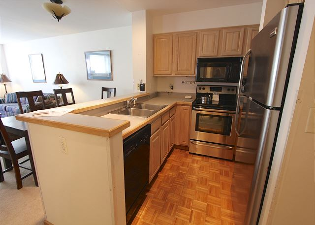 Full-sized kitchen features stainless steel appliances.