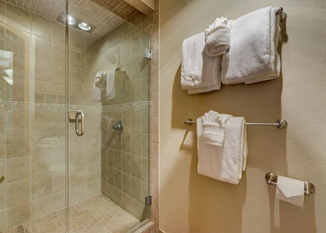 The master bathroom features beautiful tile and a glass-enclosed shower.