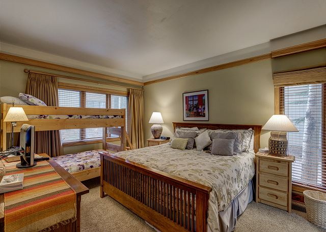The guest bedroom sleeps four with a queen-sized bed and a twin-sized bunk bed. There is a flat screen TV and this bedroom has its own access to the guest bathroom.