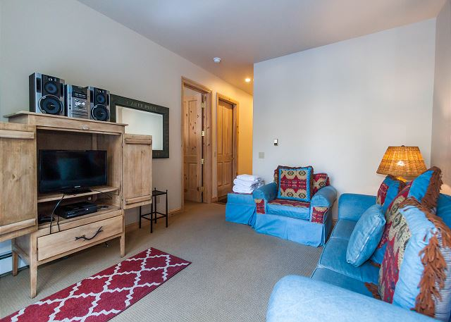 The den features a flat screen TV, a queen-sized sleeper sofa and a walk-out patio.