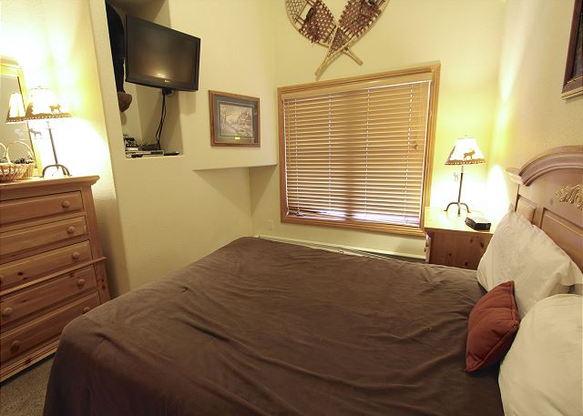 Guest bedroom features a full-sized bed and a flat screen TV.