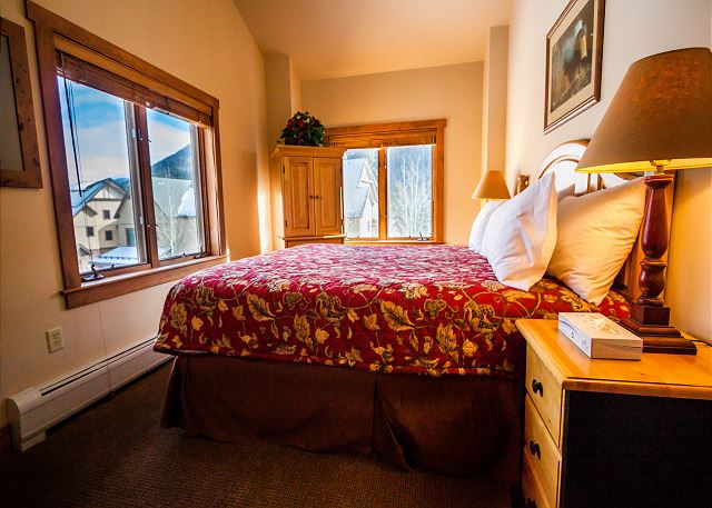The master bedroom features a king-sized bed and a television.