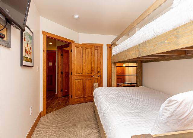 The guest bedroom features a twin-over-queen bunk bed with our Ivory White bedding and a mounted flat screen TV.