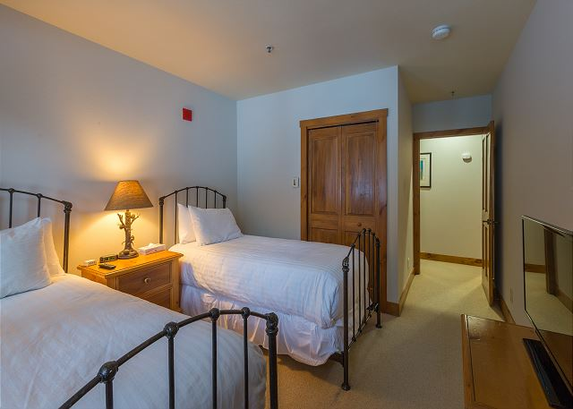 The guest bedroom features two twin-sized beds with Ivory White Bedding and a flat screen TV.