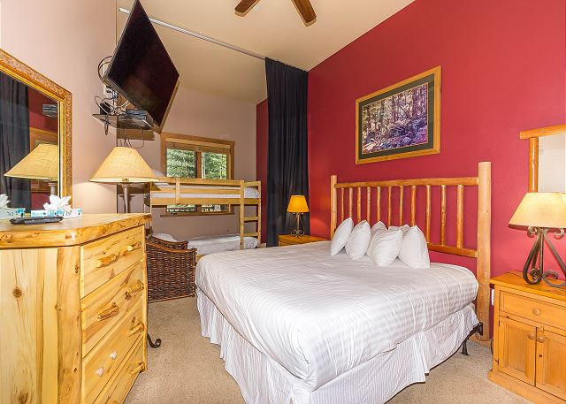 The bedroom sleeps four with a king-sized bed and a twin-sized bunk bed. The beds feature Ivory White Bedding and a mounted flat screen TV.