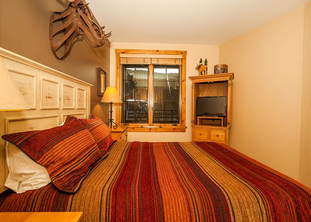 The bedroom features a queen-sized bed, a flat screen TV and beautiful ski slope views.