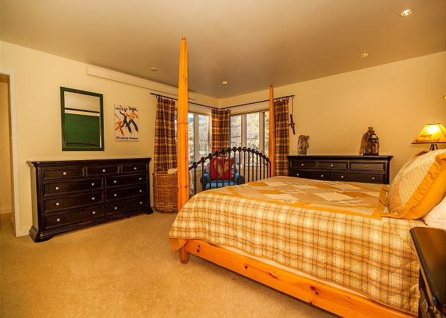 The master bedroom features a king-sized bed, large corner windows and an en suite bathroom.