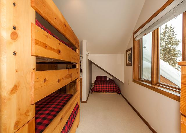 The first guest bedroom sleeps six with a queen-sized bunk bed with a trundle and a twin-sized bed.