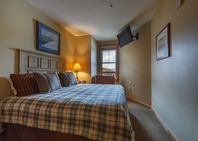 The second guest bedroom features a king-sized bed and a flat screen TV.