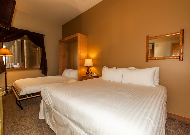 The bedroom features a king-sized bed and a queen-sized Murphy bed, both with Ivory White Bedding. There is a mounted flat screen TV.
