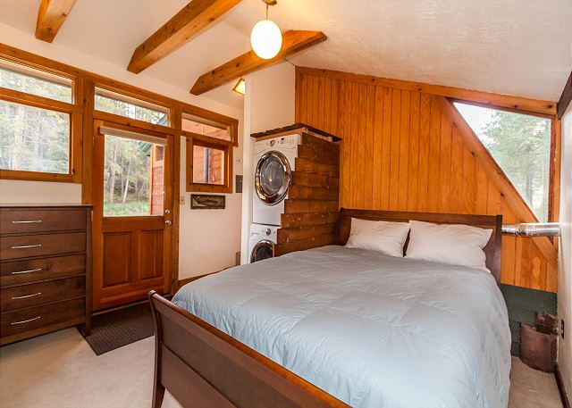 The first bedroom features a queen-sized bed and access to the private deck.
