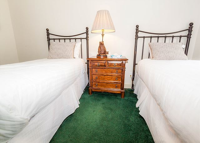 The guest bedroom features two twin-sized beds with Ivory White Bedding, a flat screen TV and access to the private patio. It also has its own private bathroom.