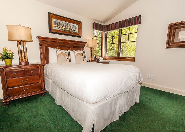 The first master bedroom features a queen-sized bed with Ivory White Bedding and a flat screen TV.