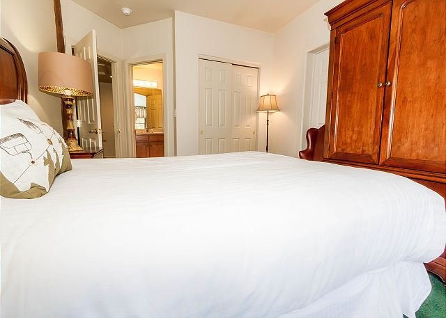 The second master bedroom features a queen-sized bed with Ivory White Bedding and a flat screen TV.