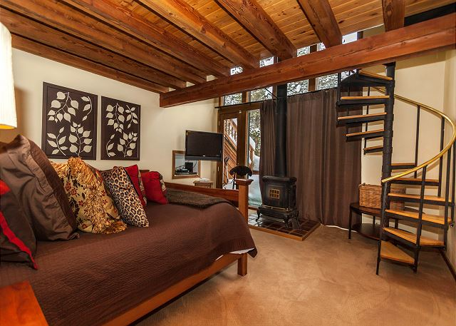 The first master bedroom features a king-sized, a flat screen TV, a wood-burning stove and its own private deck. The spiral staircase leads to a loft with a dedicated workspace and a full-sized futon.