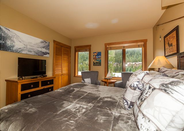 The first guest bedroom features a queen-sized bed, a flat screen TV and its own access to one of the guest bathrooms.