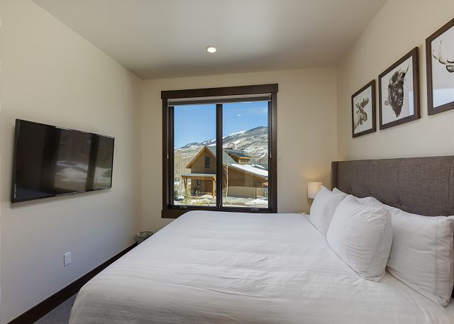 The first guest bedroom features a king-sized bed with Ivory White Bedding and a mounted flat screen TV.