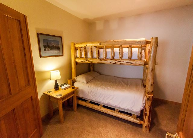 The second guest bedroom has bunk bed with a twin-sized bed on top and a full-sized bed on the bottom, both with Ivory White Bedding.
