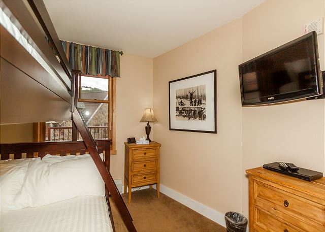 The guest bedroom features a bunk with Ivory White bedding and a mounted flat screen TV.