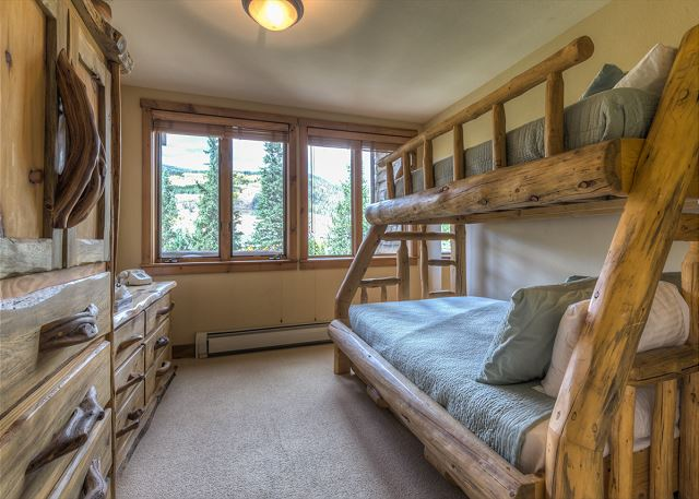 The guest bedroom features a bunk bed with a full-sized bed on the bottom, a twin on the top and a trundle that pulls out from underneath. There is also a flat screen TV and an en suite bathroom.