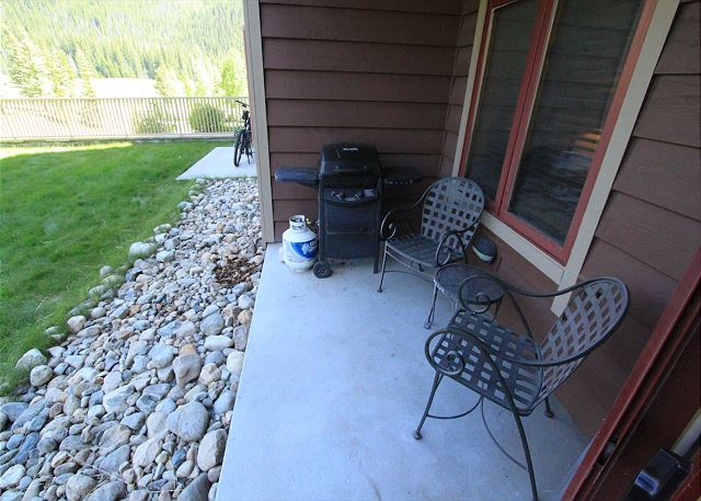 Private patio features seating and a grill.