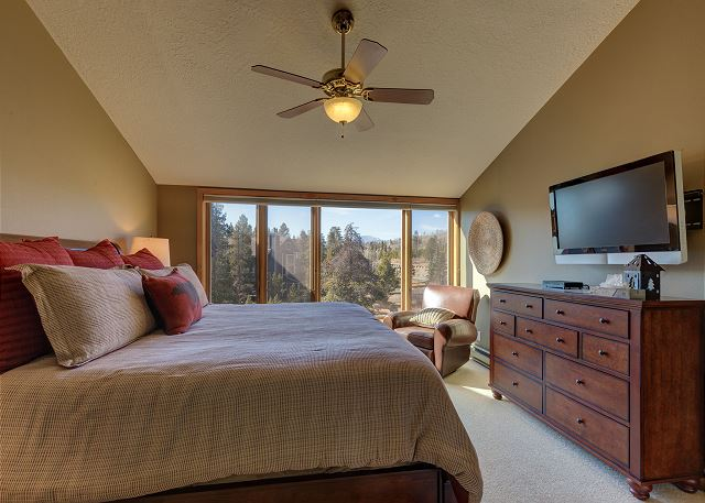 The master bedroom features a king-sized bed, a mounted flat screen TV and a wall of windows with mountain and treed views.