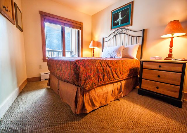 The guest bedroom features a queen-sized bed and a television.