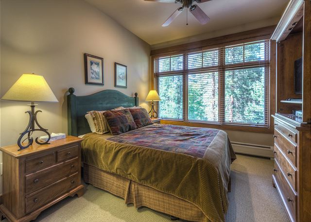 The master bedroom features a queen-sized bed, flat screen TV and an en suite bathroom.