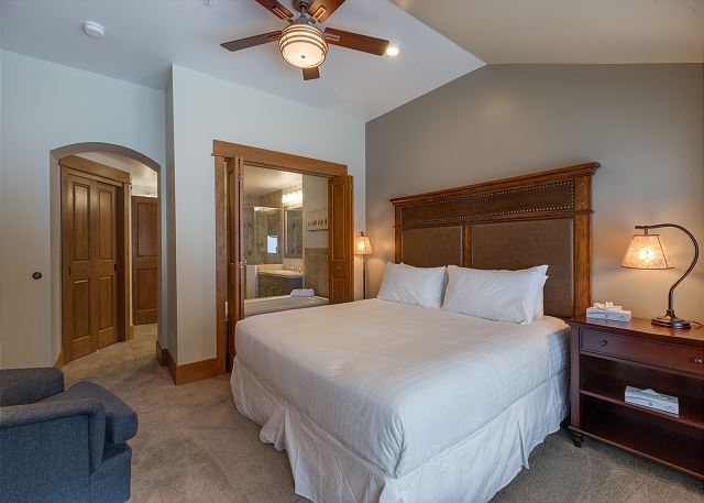The first master bedroom features a king-sized with Ivory White Bedding, a flat screen TV and beautiful ski slope views.