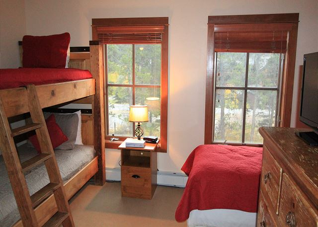 The guest bedroom features a twin-sized bed and twin-sized bunk bed, and a flat screen TV.