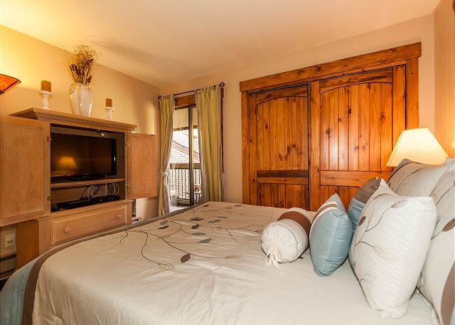 The first bedroom features a queen-sized bed, a flat screen TV and its own access to the private balcony.