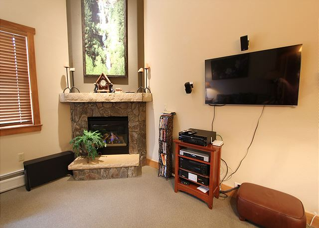 The living room features a flat screen TV and a gas fireplace.