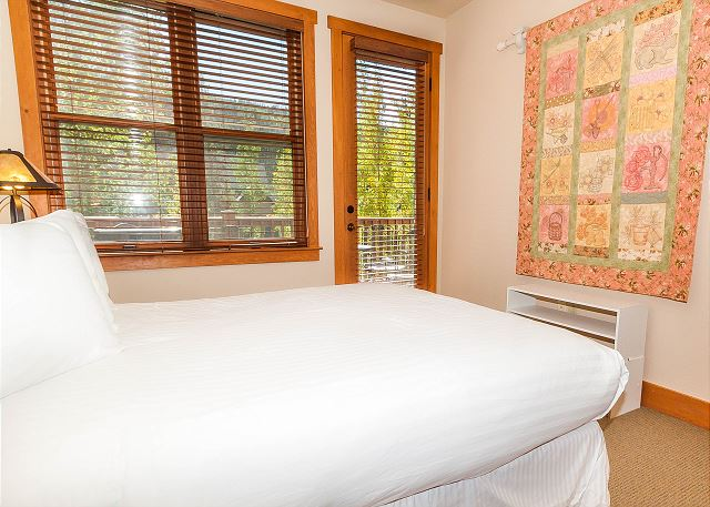 The second master bedroom is on the main level and features a queen-sized bed with Ivory White Bedding and its own entrance to the private deck.