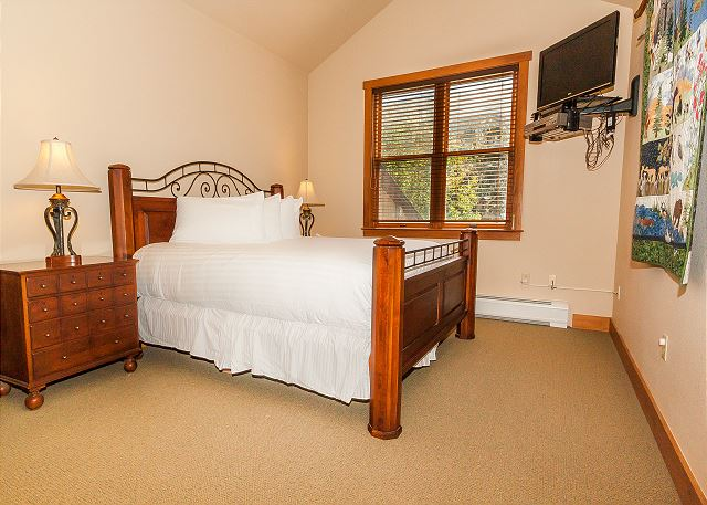 The first master bedroom is upstairs and features a king-sized bed with Ivory White Bedding and a mounted flat screen TV.