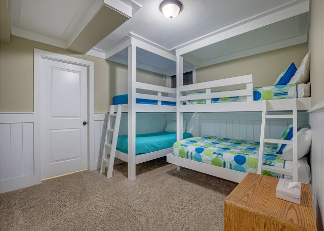 The first bedroom in the basement has two bunk beds, as well as an attached laundry room.