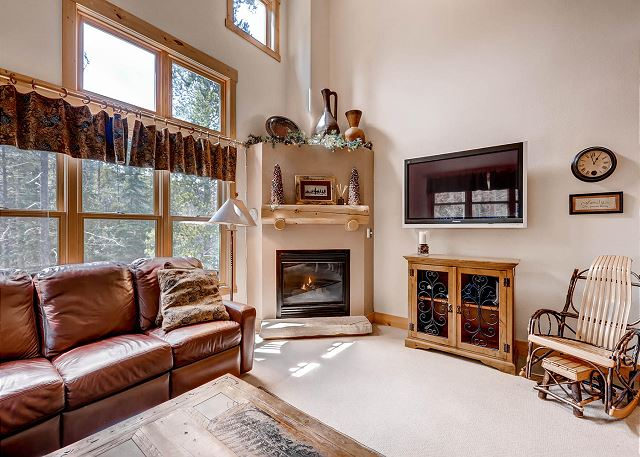 The living area features a mounted flat screen TV next to a beautiful gas fireplace and scenic views.