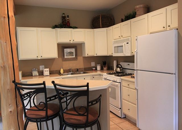Full-sized kitchen with seating at the breakfast bar.