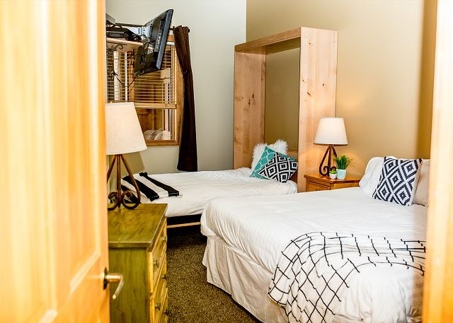 The bedroom features a king-sized bed and a queen-sized Murphy bed with Ivory White Bedding. There is also a mounted flat screen TV.