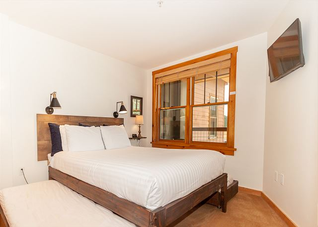 The guest bedroom features a queen-sized bed with two twin trundles and a mounted flat screen TV.