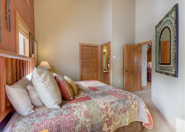 The second master bedroom features a king-sized bed, a flat screen TV and slope views.