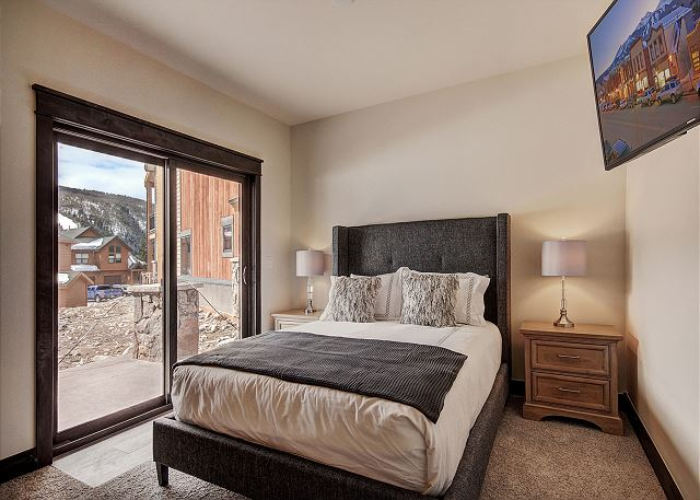 The second master bedroom features a queen-sized bed, a mounted flat screen TV and its own private patio.