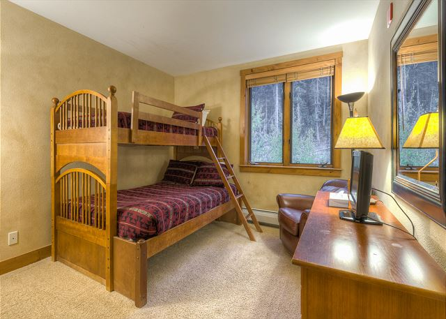 The guest bedroom features a bunk bed with a full-sized bed on the bottom and a twin on top and a flat screen TV.
