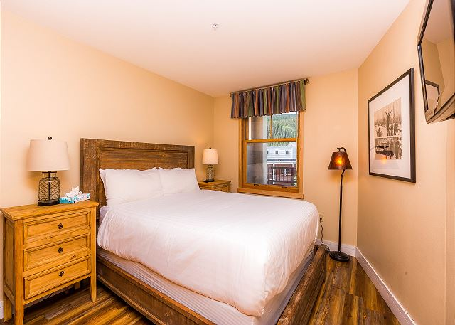 The guest bedroom features a queen-sized bed with Ivory White Bedding and a mounted flat screen TV.