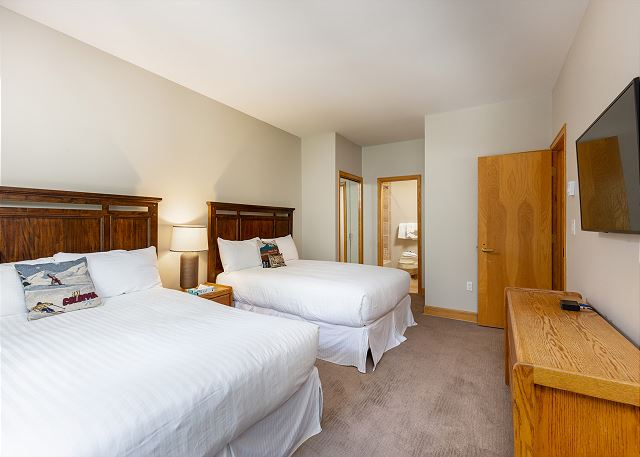 The second bedroom features two full-sized beds, a television and an en suite bathroom.