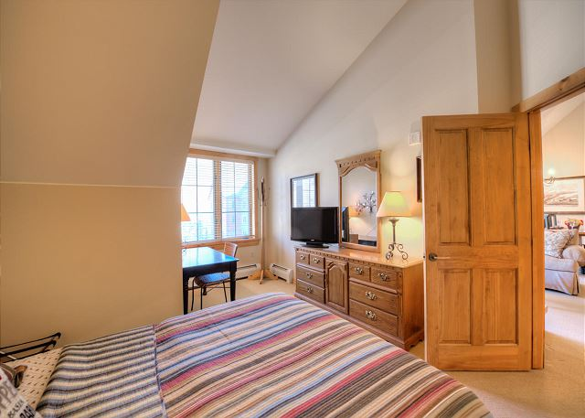 The bedroom features a queen-sized bed, a flat screen TV and a dedicated workspace.