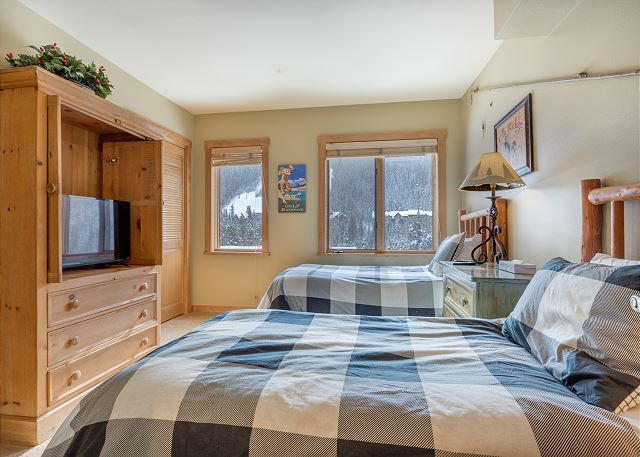 The first guest bedroom features two twin-sized beds, a flat screen TV and its own access to one of the guest bathrooms.