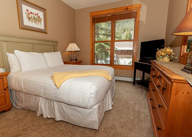 The master bedroom features a queen-sized bed and a flat screen TV.