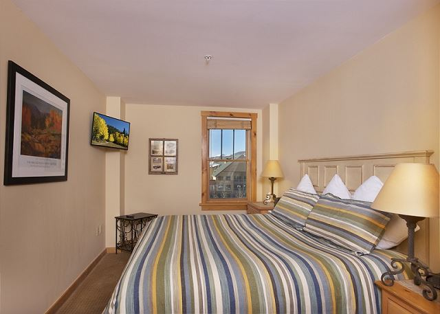 Master bedroom features a king-sized bed and a mounted flat screen TV.