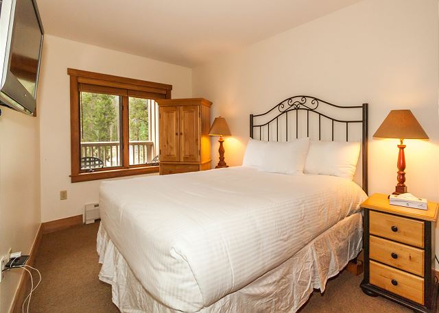 The guest bedroom features a queen-sized bed on our Ivory White Bedding program and a mounted flat screen TV.