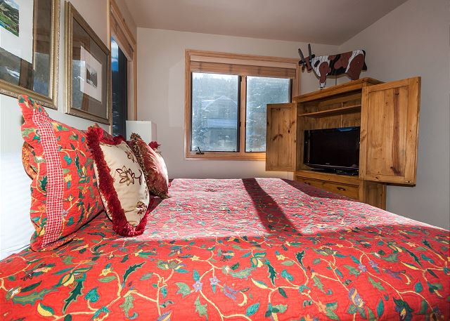 The first guest bedroom features a king-sized bed and a flat screen TV.